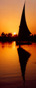 Silhouette and reflection of an elegant felucca at sunset. The River Nile, Egypt.